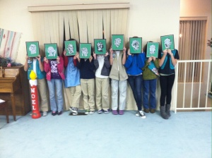 Troop 1094 in the clubhouse with the typographic silhouettes they made featuring words from the Girl Scout Promise and Law. The silhouettes will be given to their parents as Christmas presents.